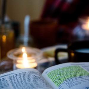 I förgrunden en uppslagen bibel. I bakgrund ljuslykta, kaffekopp och tillbehör.