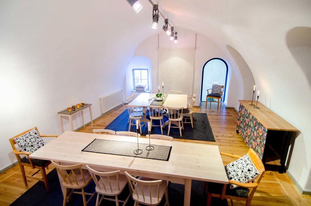 Rum med valvat stentak i vitt. Möblerat med två stora bord och stolar.