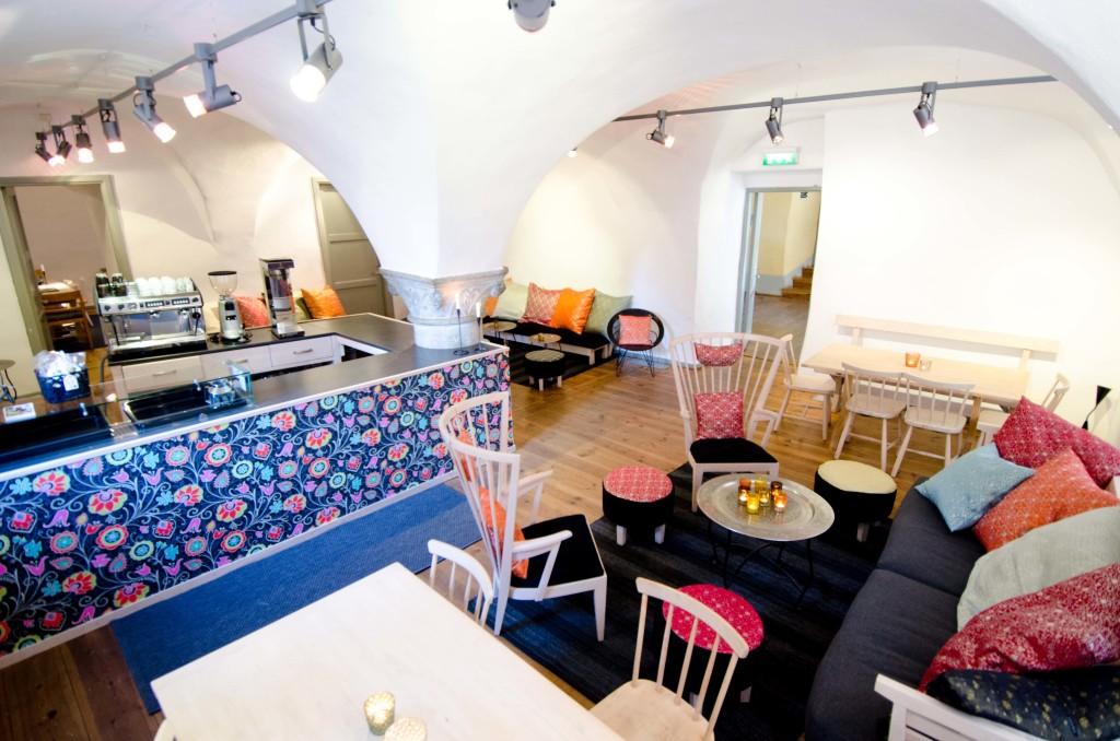 CAfé med valvat stentak och en pelare i mitten. Möblerat med bord, stolar och soffor. En kafédisk i mitten.