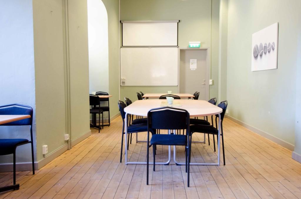Rum Josefina. Möblerat för konferensuthyrning med bord, White board tavla och projektorduk.